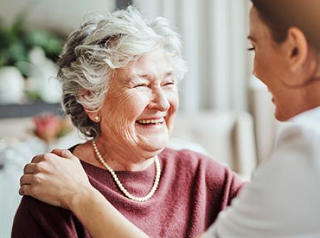 Senior smiling and talking with adult caregiver