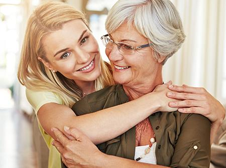 Senior and cargiver adult child hugging and laughing