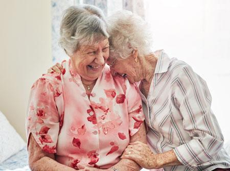 Two senior women hugging and laughing one in floral shirt and the other in plaid