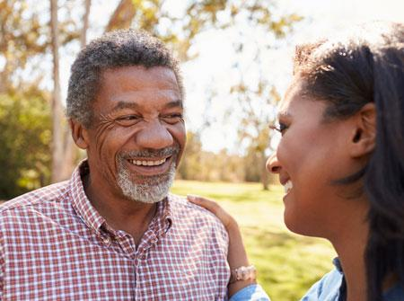 Smiling senior man outside with his adult daughter