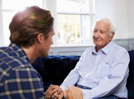 Senior sitting with younger male in plaid shirt