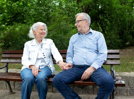 senior couple resting on a park bench holding hands