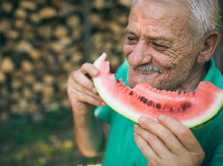 Senior smiling and eating watermelon